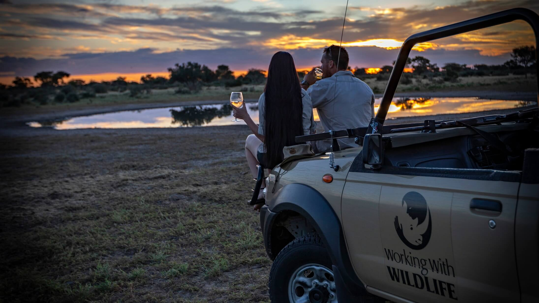 Couple drinking during sundowners as sunsets on an african safari